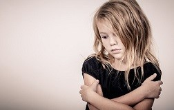 Portrait of sad blond little girl standing near wall