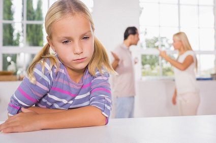 Little girl looking sad in front of fighting parents in the kitchen